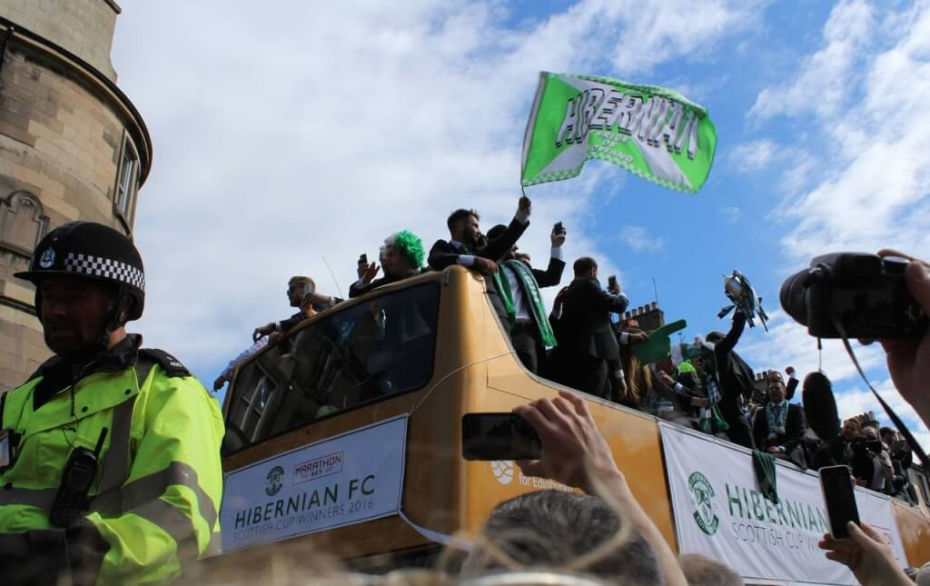 The trophy is held aloft and flag flies as Hibernian's open top bus nears the bottom of Leith Walk