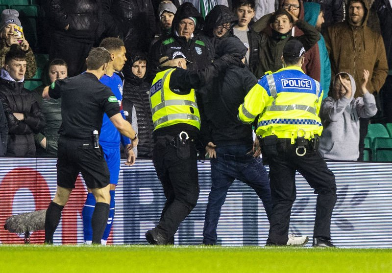 Police remove a fan who confronted James Tavernier